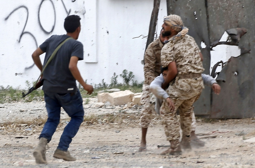 Fighters loyal to the Libyan internationally-recognized Government of National Accord (GNA) carry a wounded comrade during clashes against forces loyal to strongman Khalifa Haftar, on Tuesday in the Salah Al-Din area south of the Libyan capital Tripoli. — AFP