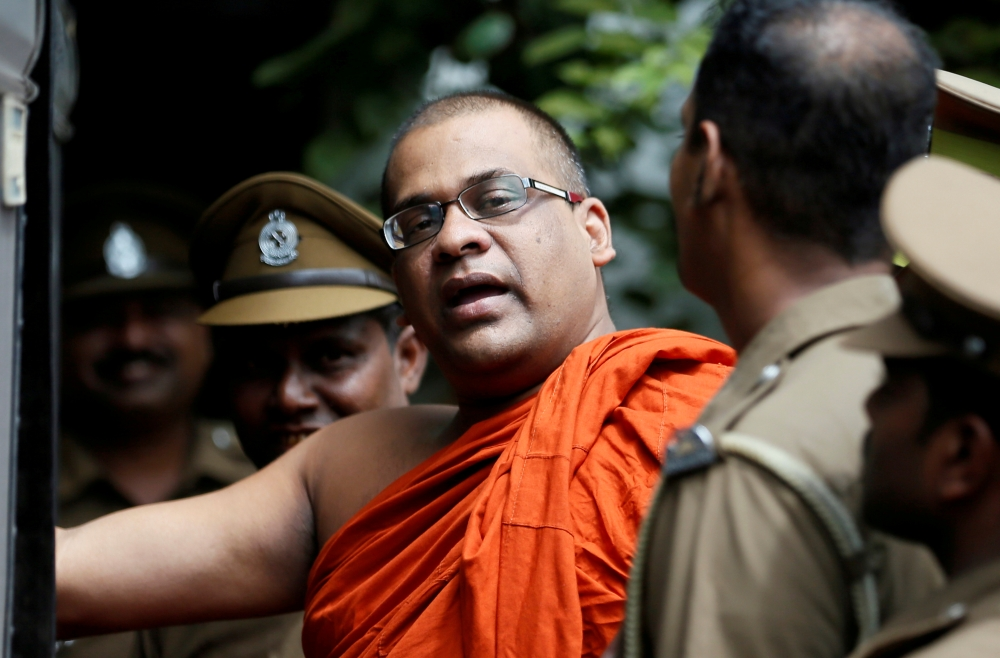 File photo shows Galagoda Aththe Gnanasara Thero, head of Buddhist group Bodu Bala Sena (BBS), walking towards a prison bus while accompanied by prison officers after he was sentenced by a court in Sri Lanka. — Reuters