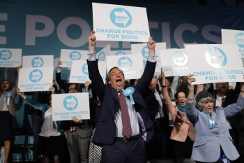 Brexit Party leader Nigel Farage (C) holds up a placard at the end of a European Parliament election campaign rally at Olympia London,  west London on Tuesday. — AFP