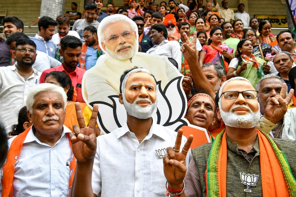 Indian supporters and party workers of Bharatiya Janata Party (BJP) wear masks of Indian Prime Minister Narendra Modi and flash victory signs as they celebrate on the vote results day for India's general election in Bangalore on Thursday. Indian Prime Minister Narendra Modi looked on course for a major victory in the world's biggest election, with early trends suggesting his Hindu nationalist party will win a bigger majority even than 2014. — AFP