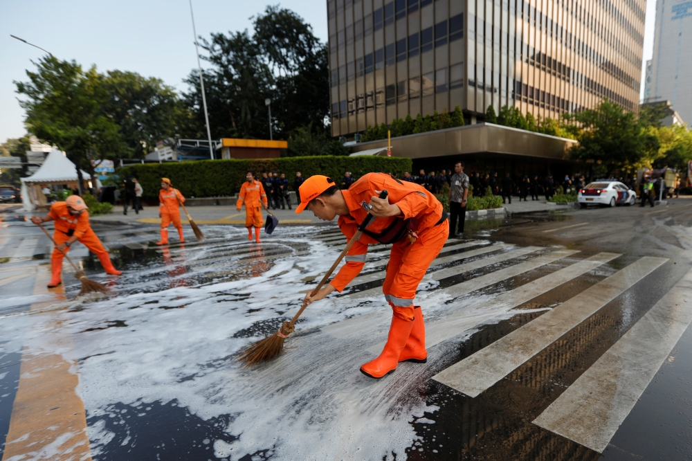 Workers clean the road after a riot outside Indonesia's Election Supervisory Agency (Bawaslu) headquarters following the announcement of last month's presidential election results in Jakarta, Indonesia, Thursday. — Reuters