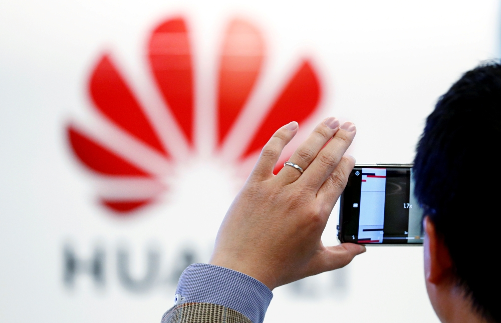 A man takes a picture of a Huawei logo at the Huawei European Cybersecurity Center in Brussels, Belgium. — Reuters