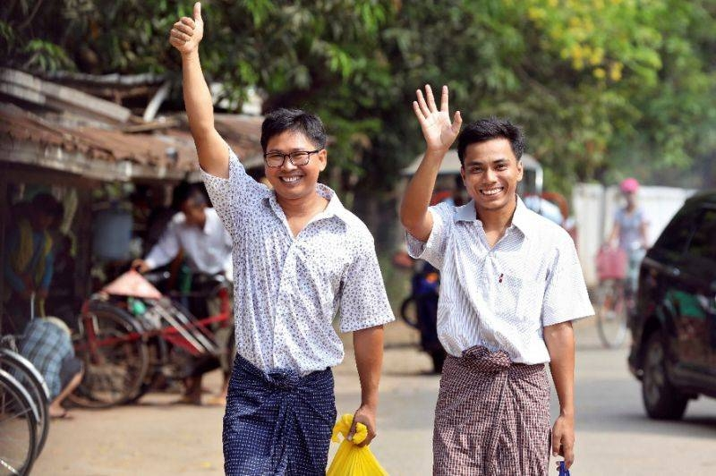 Journalists Wa Lone and Kyaw Soe Oo gesture as they walk out of Insein prison gate after being freed in a presidential amnesty in Yangon on May 7, 2019. — AFP