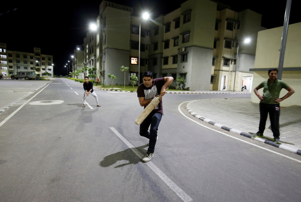 Residents play cricket under street lights at the Gujarat International Finance Tec-City (GIFT) at Gandhinagar, in the western state of Gujarat, in this file photo. — Reuters
