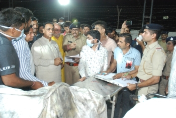 In this picture taken on Friday, Gujarat Chief Minister Vijaybhai Rupani (3 left) stand near the bodies of students, who died in a fire in a building in India housing a college, at a hospital in Surat, some 270 km, from Ahmedabad. — AFP