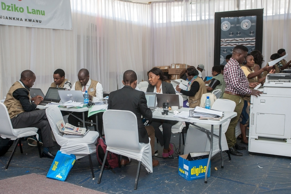 The Malawi Electoral Commission (MEC) staff members work to tabulate and tally votes heavily guarded by military personnel at the National Tally Center following the country's May 21 tripartite elections in Blantyre on Saturday. — AFP
