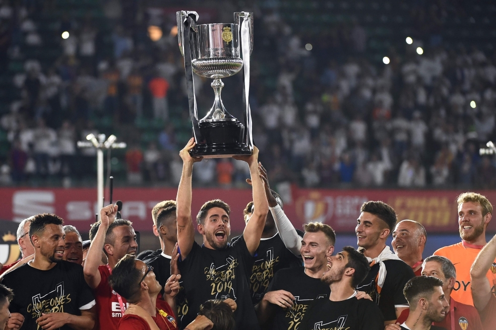 Valencia players celebrate with their trophy after winning the 2019 Spanish Copa del Rey (King's Cup) final football match between Barcelona and Valencia at the Benito Villamarin stadium in Sevilla on Saturday. — AFP
