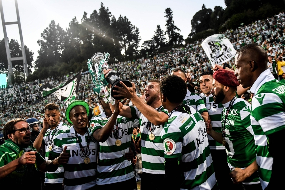 Sporting's Macedonian defender Stefan Ristovski, center, holds the trophy and celebrates with his teammates and supporters after winning Portugal's Cup final football match between Sporting CP and FC Porto at Jamor stadium in Oeiras, outskirts of Lisbon, on Saturday. — AFP