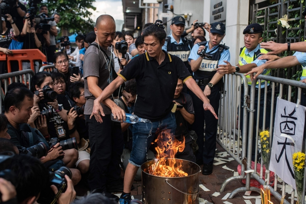 A police officer (left) puts out a fire as pro-democracy activist Lui Yuk-lin burns props outside the Chinese liaison office during a march in Hong Kong Sunday to commemorate the June 4, 1989 Tiananmen Square crackdown in Beijing. — AFP