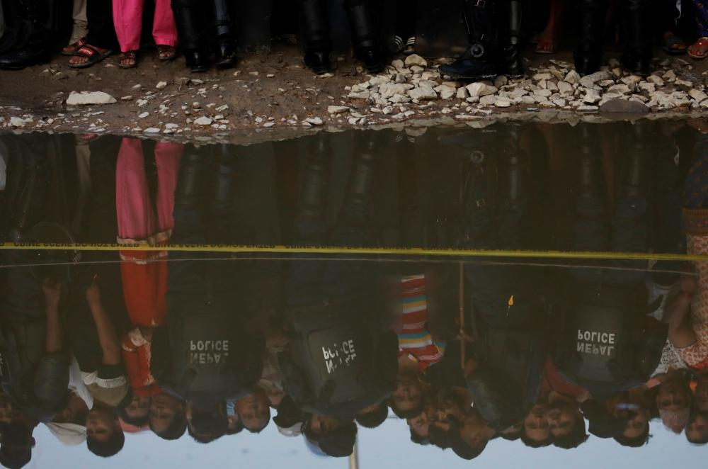 People are reflected in a puddle near an explosion site in Kathmandu on Sunday. — Reuters