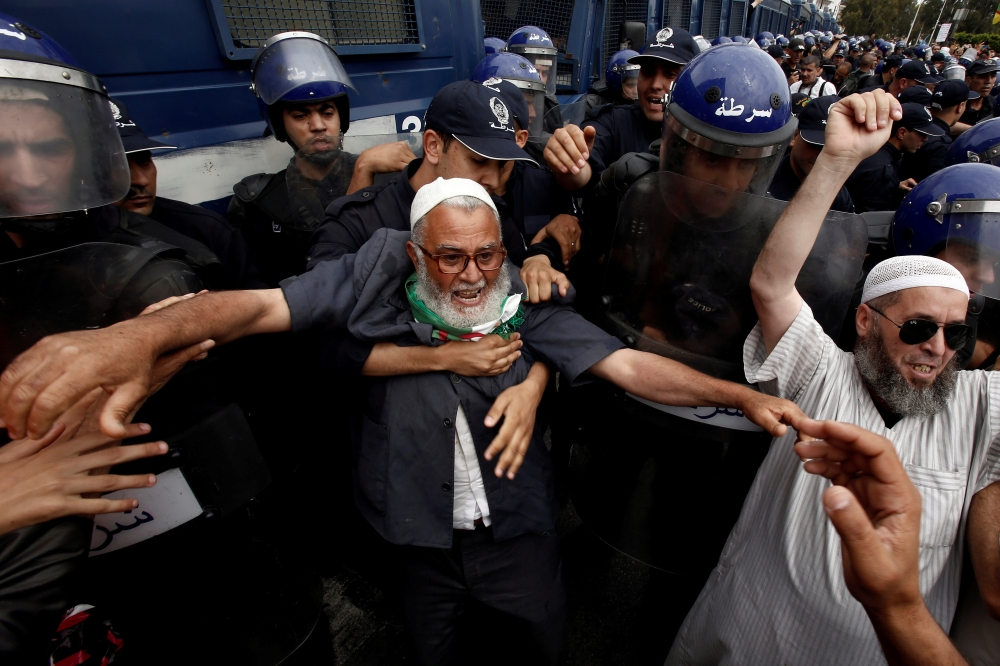 Demonstrators and police officers confront each other in Algiers during a protest to demand the postponement of a presidential election and the removal of the ruling elite. — Reuters