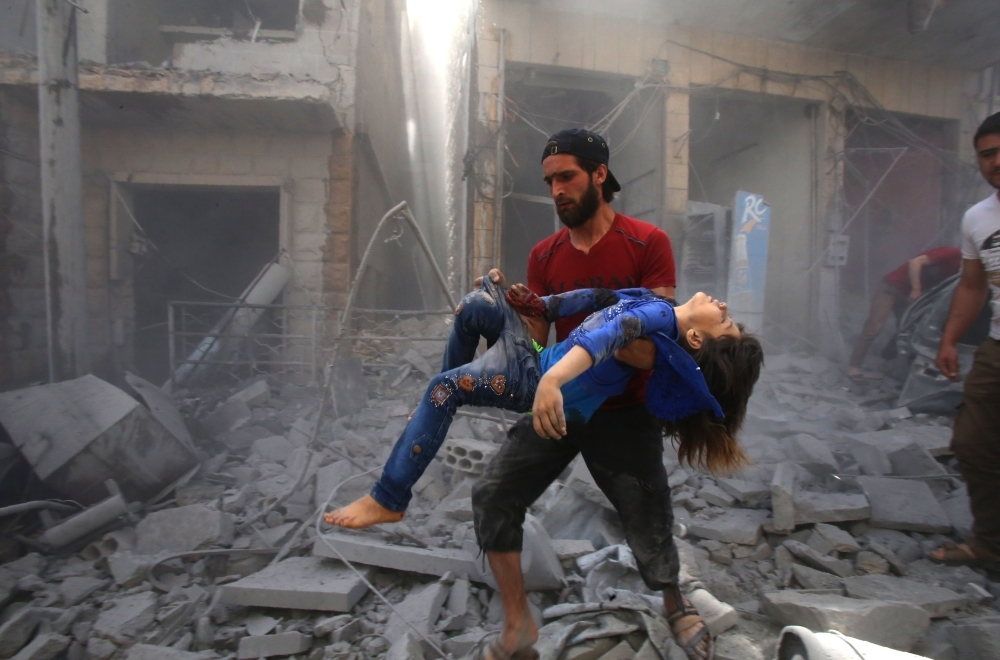 A man evacuates a young bombing casualty after a reported air strike by regime forces and their allies in the rebel-held Syrian town of Maaret Al-Noman in the southern Idlib province on Sunday. — AFP