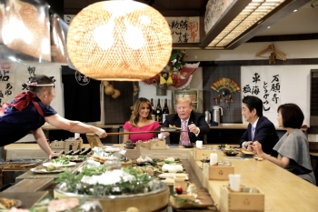 US President Donald Trump, with first lady Melania Trump, receives a plate of food from a chef as they and Japanese Prime Minister Shinzo Abe and his wife Akie Abe have a couples dinner in Tokyo, Sunday. — Reuters