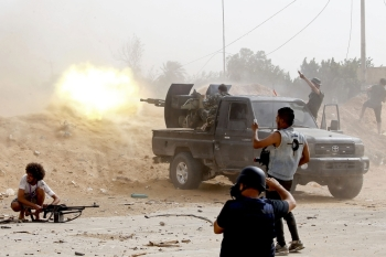 A fighter loyal to the Libyan National Accord (GNA) fires a heavy machine gun as a press photographer take pictures of the scene during clashes against forces loyal to strongman Khalifa Haftar, in the Airport Road Area, south of the Libyan capital Tripoli, on Saturday. — AFP