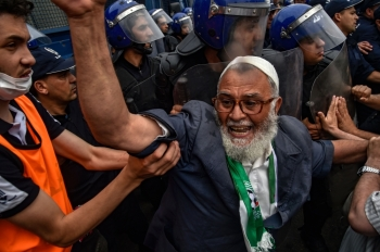 Algerian protesters gather before riot police during an anti-government demonstration outside the the Grand Post Office, a key rallying point for protesters in the capital Algiers, in this May 24, 2019 file photo. — AFP