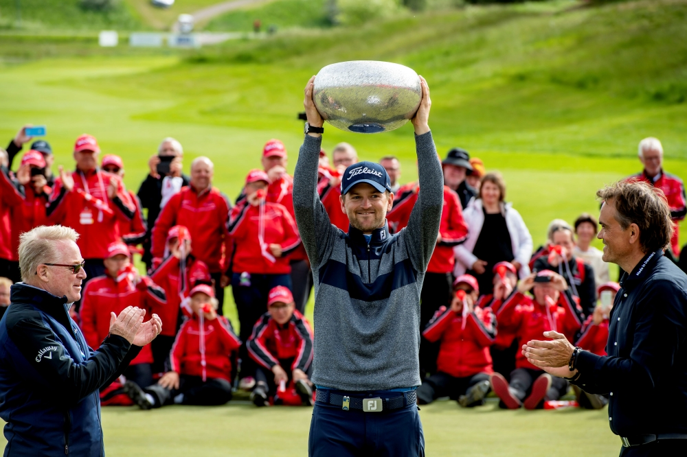 Kieth Pelley CEO European Tour and Flemming Astrup of Made in Denmark react as Bernd Wiesberger of Austria holds a trophy as he won Made in Denmark 2019 in Gatten, Denmark, on Sunday. — Reuters