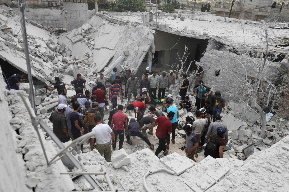 Syrian rescue teams and civilians look for survivors in a heavily damaged area following a reported air strike by regime forces and their allies on the market town of Kfar Ruma in Syria's southwestern Idlib province, on Thursday. — AFP