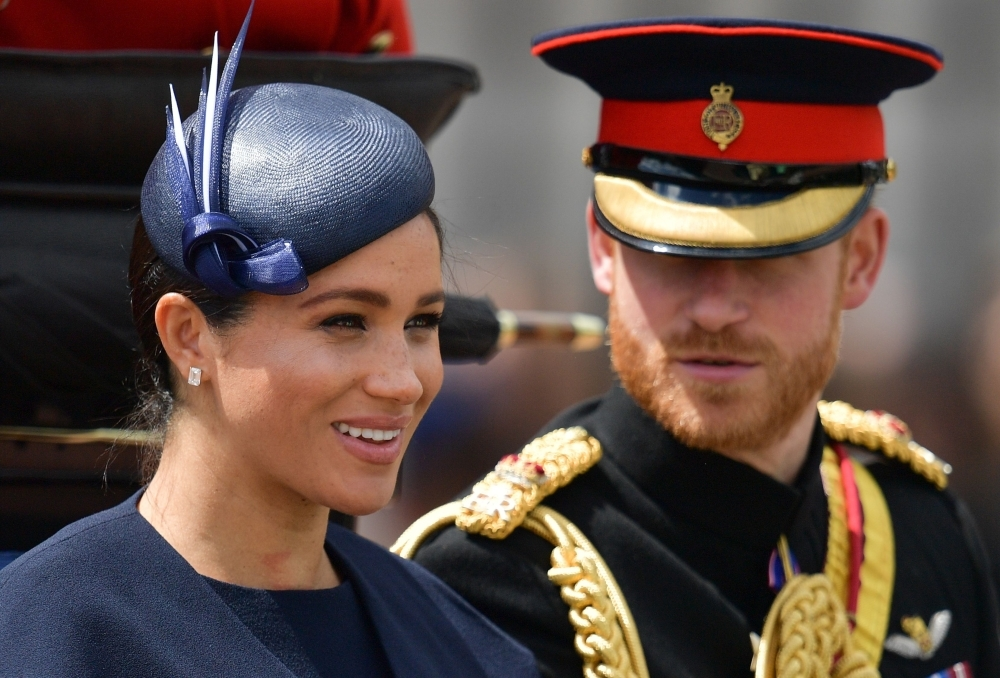 Britain's Meghan, Duchess of Sussex (L) and Britain's Prince Harry, Duke of Sussex (R) return to Buckingham Palace after the Queen's Birthday Parade, 'Trooping the Colour', in London on Saturday. — AFP