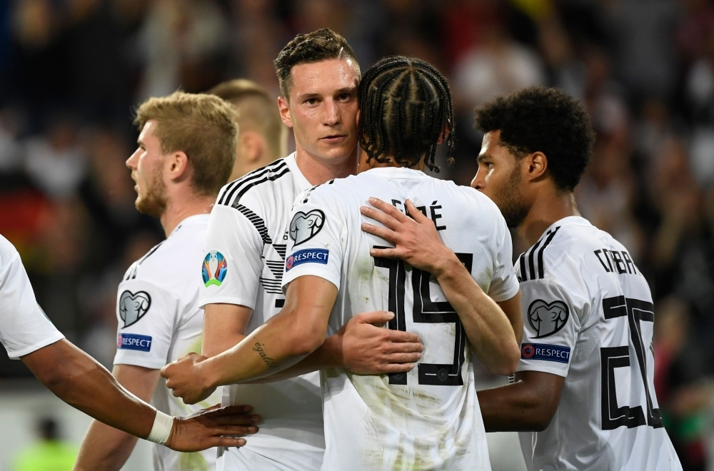 Germany's forward Julian Draxler, left, and Germany's midfielder Leroy Sane celebrate after the 8-0 victory in the UEFA Euro 2020 qualifier Group C football match Germany against Estonia in Mainz, Germany, on Tuesday. — AFP