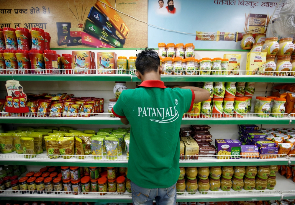 A worker arranges consumable goods inside a Patanjali store in Ahmedabad, India, in this March 28, 2019 photo. — Reuters