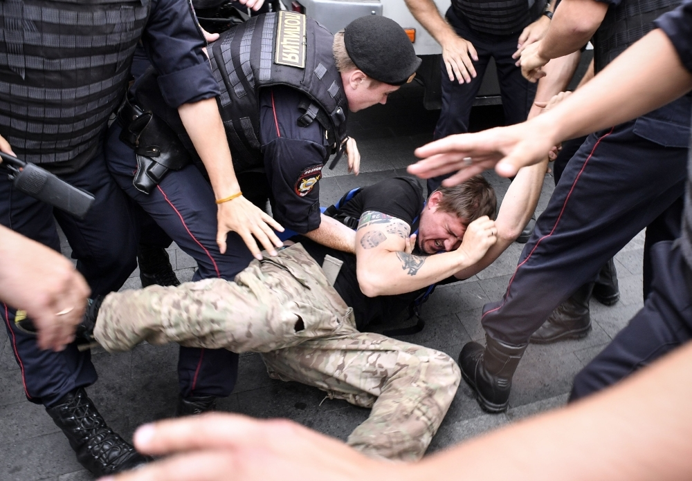 Russian police officers detain a protestor during a march to protest against the alleged impunity of law enforcement agencies in central Moscow on Wednesday. — AFP