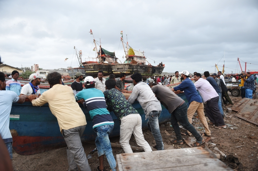 Indian fishermen push a fishing boat out of the sea as a part of precautionary measures as Cyclone Vayu nears the Gujarat coastline at Veraval Port, some 400 Kms. from Ahmedabad on Wednesday. — AFP