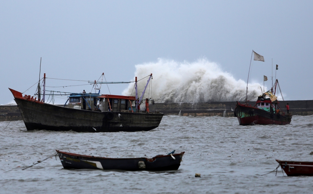 Waves crash against the jetty at a fishing harbor ahead of the expected landfall of Cyclone Vayu at Veraval, India, Wednesday. — Reuters