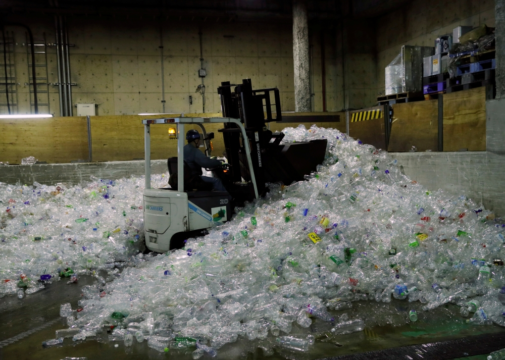 A forklift car carries PET bottles for recycling at Minato Resource Recycle Center in Tokyo, Japan. — Reuters