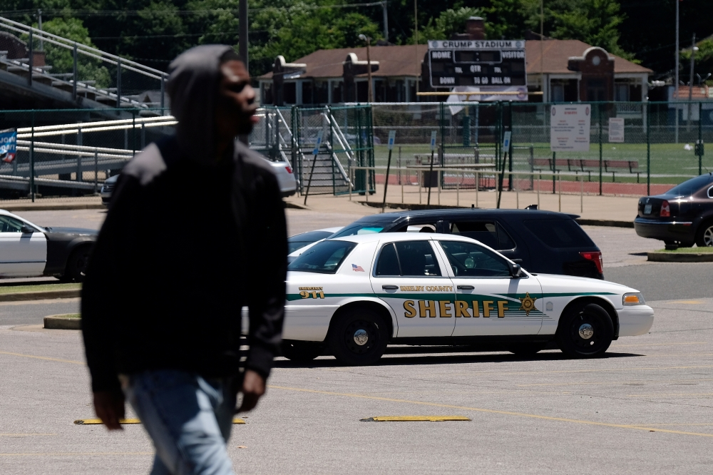 A young man walks in front of a police patrol parked in front of a high school a day after violent clashes between police and protesters broke out on streets overnight in Memphis, Tennessee, US, Thursday. — Reuters