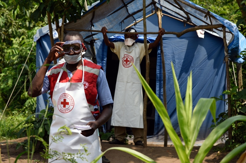 Health workers stand at a non-gazetted crossing point in the Mirami village, near the Mpondwe border check point between Uganda and the Democratic Republic of Congo, Friday. — AFP
