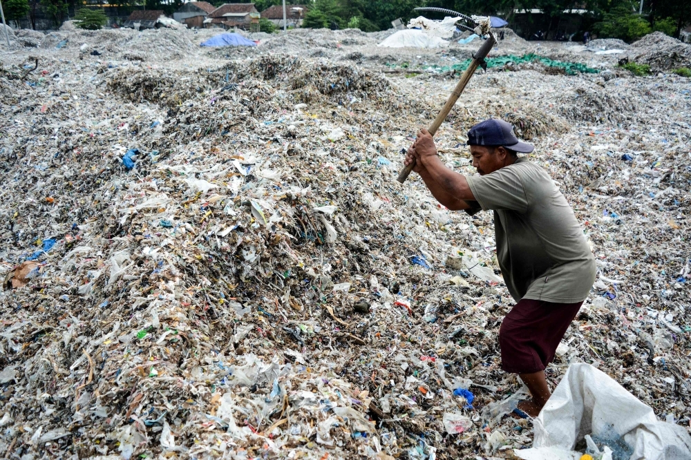 A man searches for plastic waste for resale at a dump in Mojokerto, East Java province. Around 300 million ton of plastic are produced every year and end up in landfill or the seas, according to the Worldwide Fund for Nature. — AFP