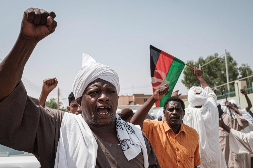 People react as they leave a mosque where Sudanese top opposition leader and former premier attended Friday prayers in the capital Khartoum's twin city Omdurman. — AFP