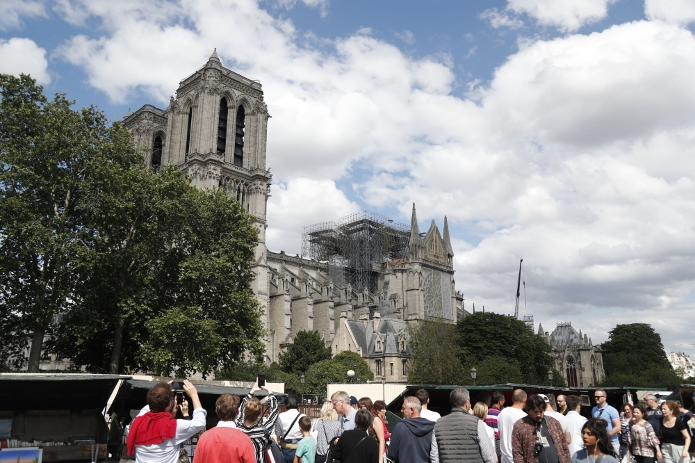 People walk along the banks of the River Seine past the Notre-Dame de Paris cathedral, in Paris on Saturday. — AFP
