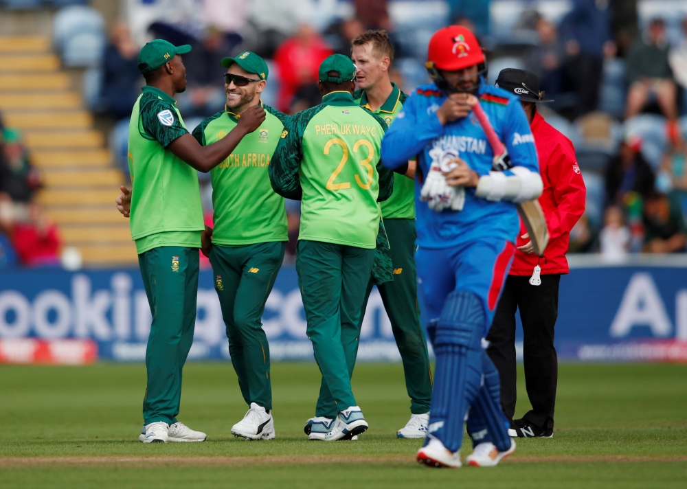 South Africa's Chris Morris celebrates with Faf du Plessis and teammates after taking the wicket of Afghanistan's Hamid Hassan during the ICC Cricket World Cup match at Cardiff Wales Stadium, Cardiff, Britain, on Saturday. — Reuters