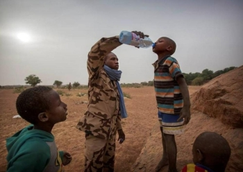 A member of MINUSMA Chadian contingent gives water to a boy in Kidal, Mali December 17, 2016. — Reuters