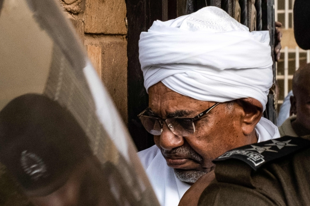 Sudan's ousted president Omar Al-Bashir is escorted into a vehicle as he returns to prison following his appearance before prosecutors over charges of corruption and illegal possession of foreign currency, in the capital Khartoum on Sunday. — AFP