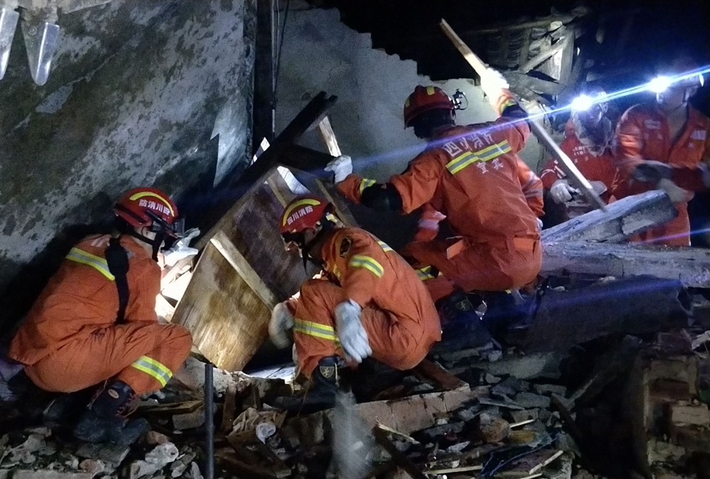 Rescuers search for earthquake survivors in the rubble of a building in Yibin, in China's southwest Sichuan province, early on Tuesday. — AFP