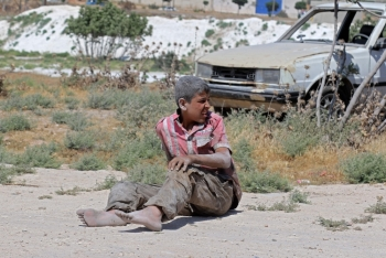 A young Syrian man sits on the ground after a bombing on an industrial area of Idlib, northern Syria, on Monday. — AFP