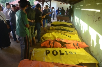 Indonesian villagers examine victims of a ferry accident in Dungkek, East Java, on Tuesday. — AFP