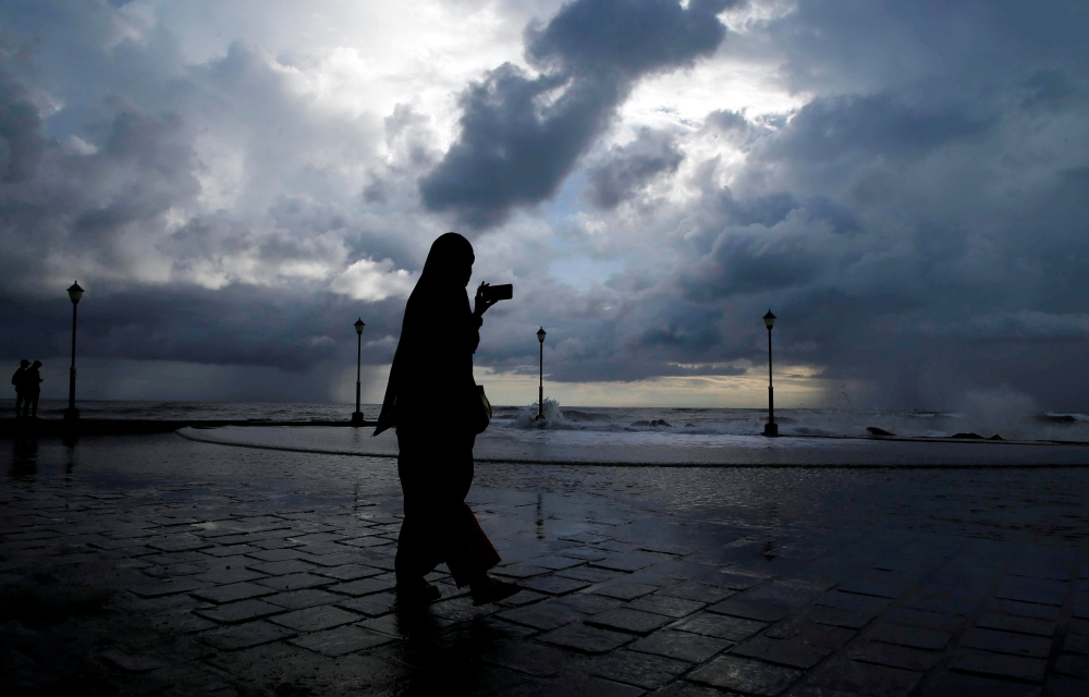 A woman takes photographs with her mobile phone against the backdrop of monsoon clouds at a beach in the south Indian city of Kochi, last week. — Reuters