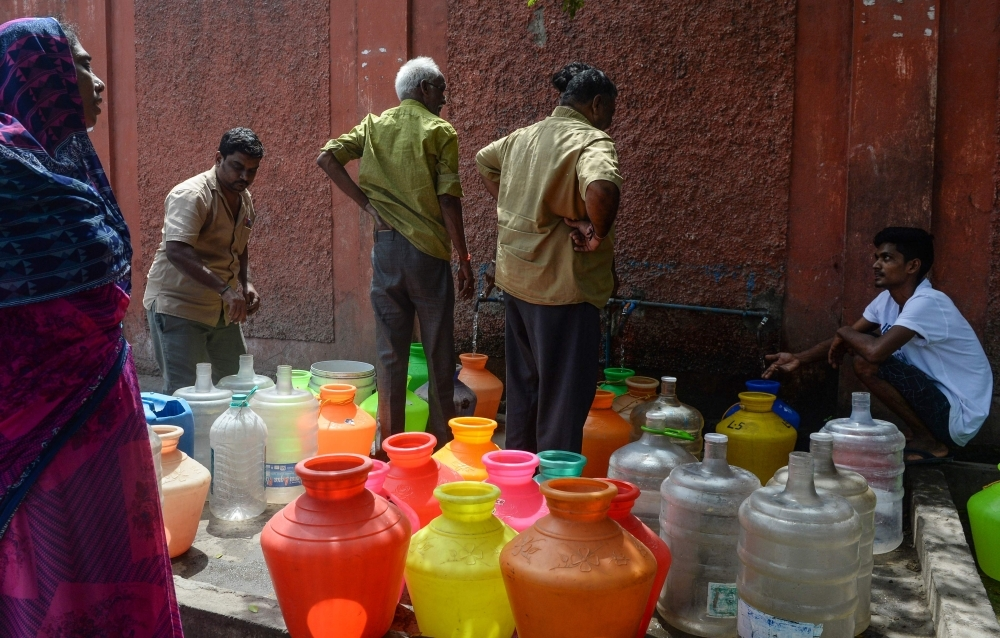 Indian residents stand around with plastic pots filled with drinking water at a distribution point in Chennai on Wednesday. — AFP