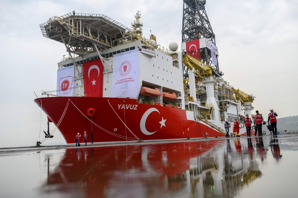 Journalists walk next to the drilling ship 'Yavuz' scheduled to search for oil and gas off Cyprus, at the port of Dilovasi, outside Istanbul, on Thursday. — AFP