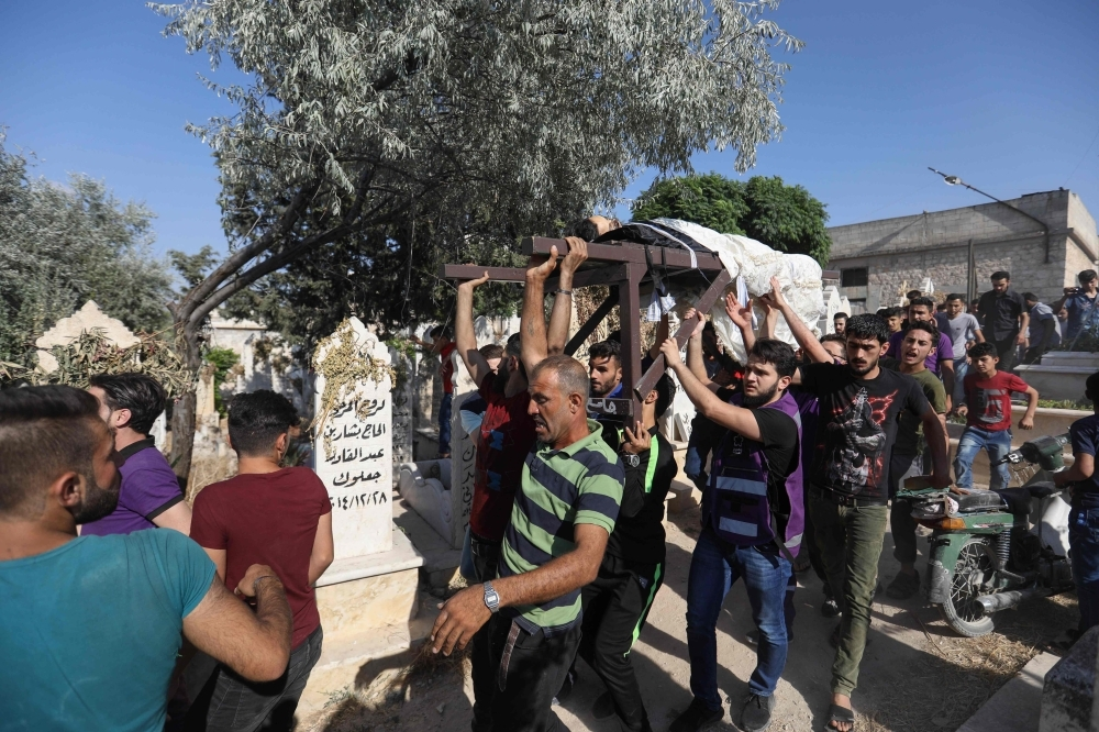 Syrians carry the body of a rescue worker, who was killed in a reported regime air strike, during his funeral in the town of Maaret Al-Numan in northwest Syria on Thursday. — AFP