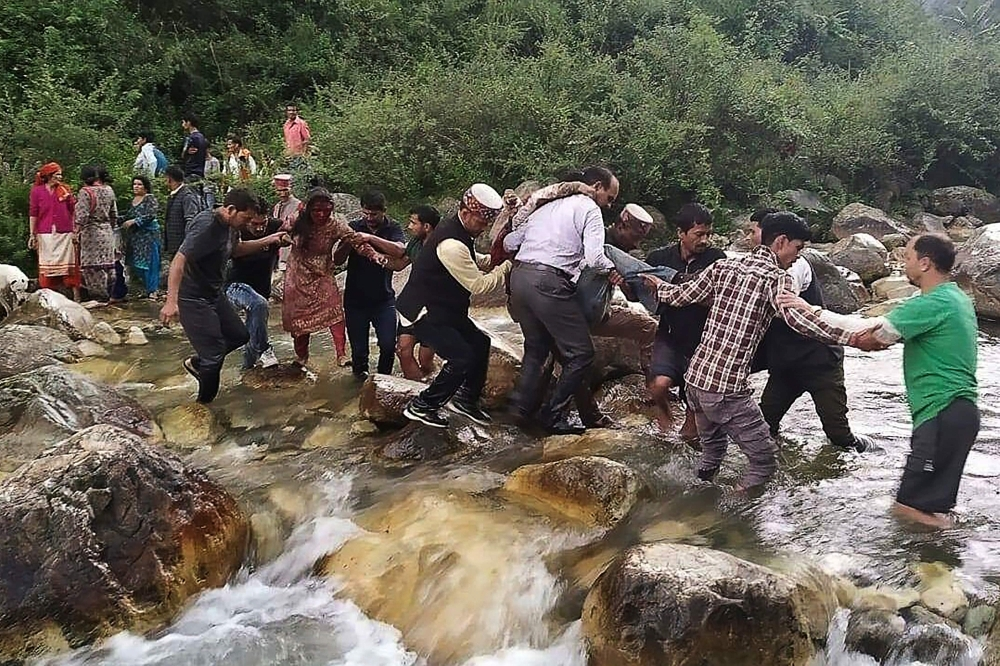 Local residents help accident survivors cross a river after a bus carrying some 50 passengers fell into a 150-meter (500-foot) gorge near Banjar, in the mountainous Kullu district of the Indian state of Himachal Pradesh, on Thursday. — AFP