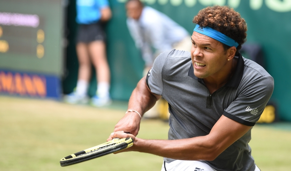 Jo-Wilfried Tsonga from France  returns to Roger Federer from Switzerland at the ATP tennis tournament in Halle, western Germany, on Thursday. — AFP