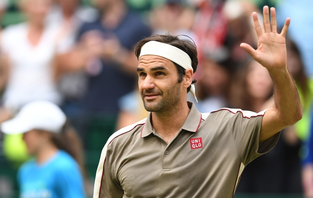 Switzerland's Roger Federer celebrates after winning against France's Jo-Wilfried Tsonga during their tennis match at the ATP Open tennis tournament in Halle, western Germany, on Thursday. — AFP
