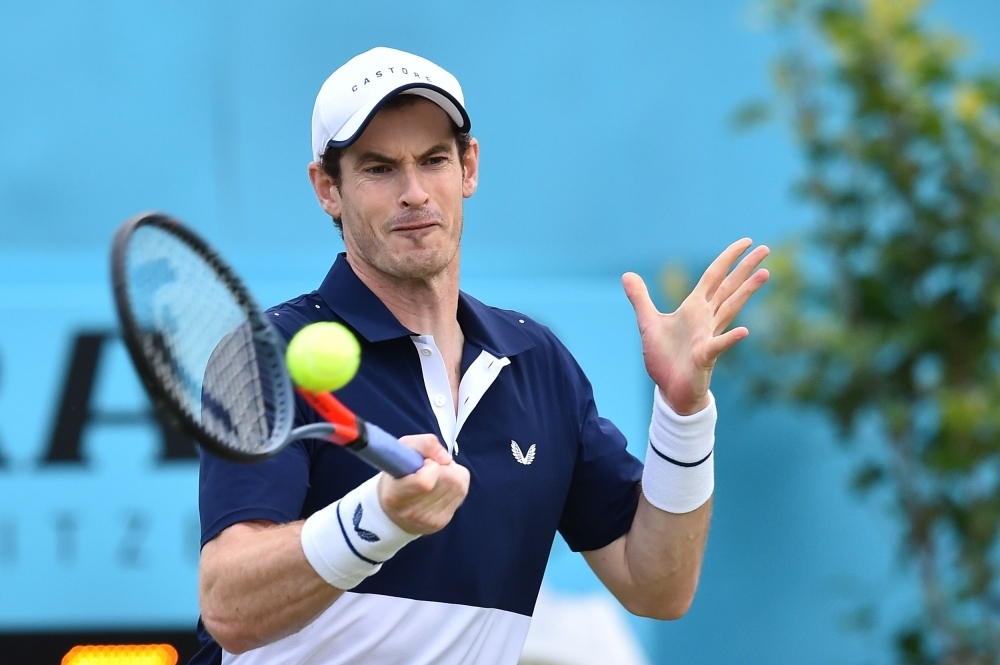 Britain's Andy Murray returns to Colombia's Juan Sebastian Cabal and Robert Farah during a first round doubles match at the ATP Fever-Tree Championships tennis tournament at Queen's Club in west London on Thursday. — AFP