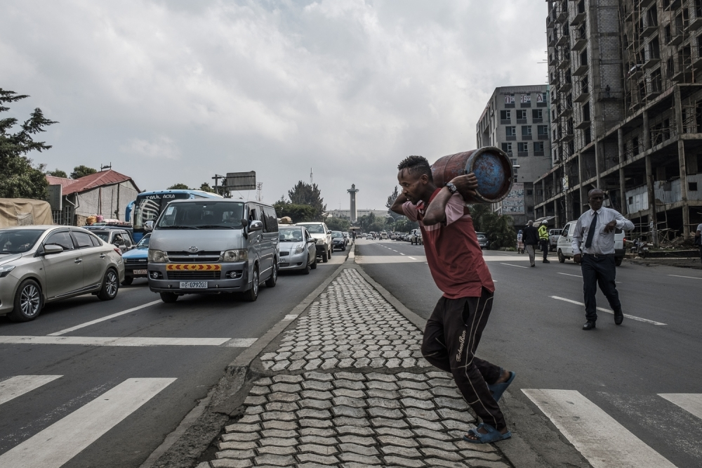 A man carries a gas cylinder as he makes his way across the central street in the capital Addis Ababa on Monday. — AFP