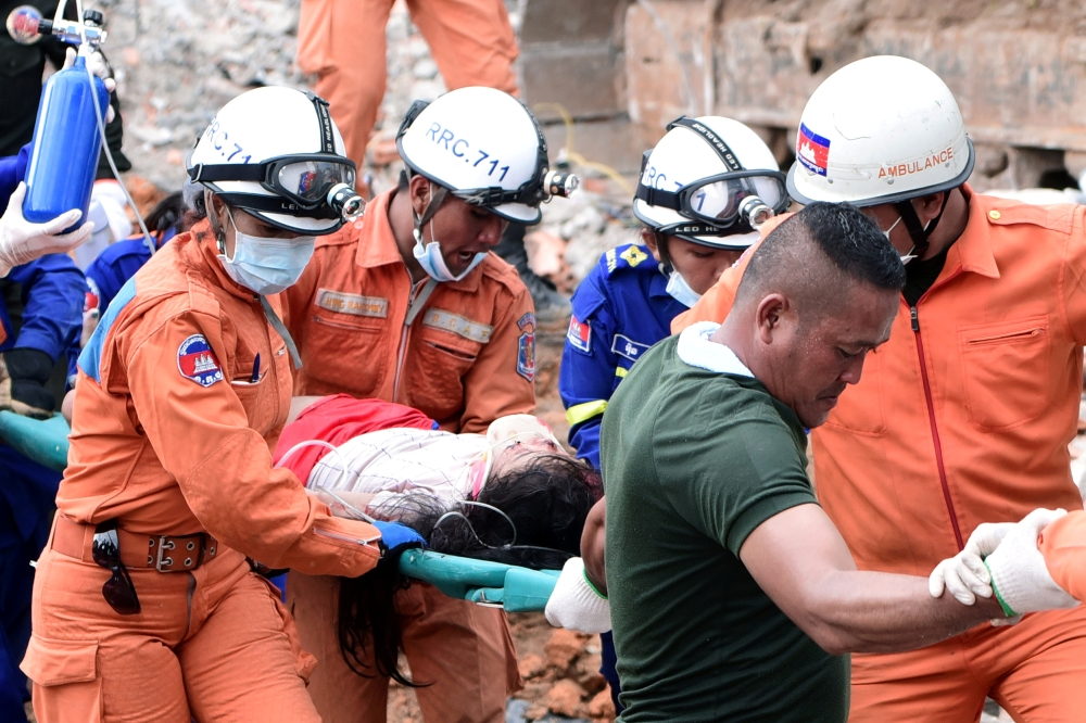 A rescue team carries a wounded worker at a collapsed building in Sihanoukville, Cambodia, Saturday. -Reuters