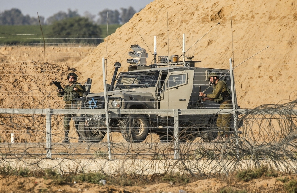 Israeli soldiers are seen next to a military vehicle across the barbed-wire border fence with the Gaza Strip during clashes following a Palestinian demonstration east of Khan Yunis, in this file photo. — AFP